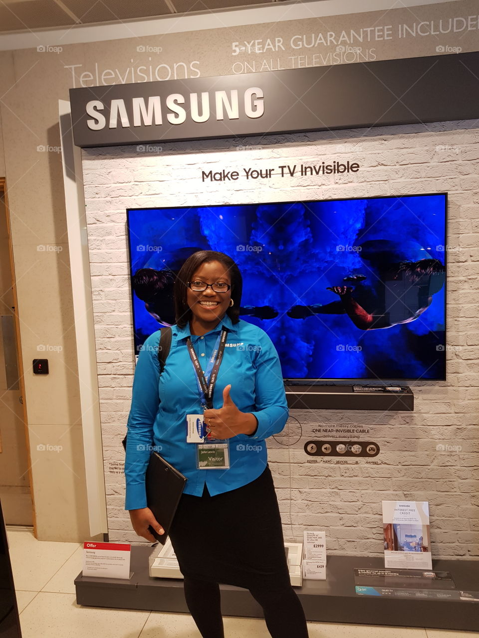 Samsung QLED television with soundbar on display wall and field force