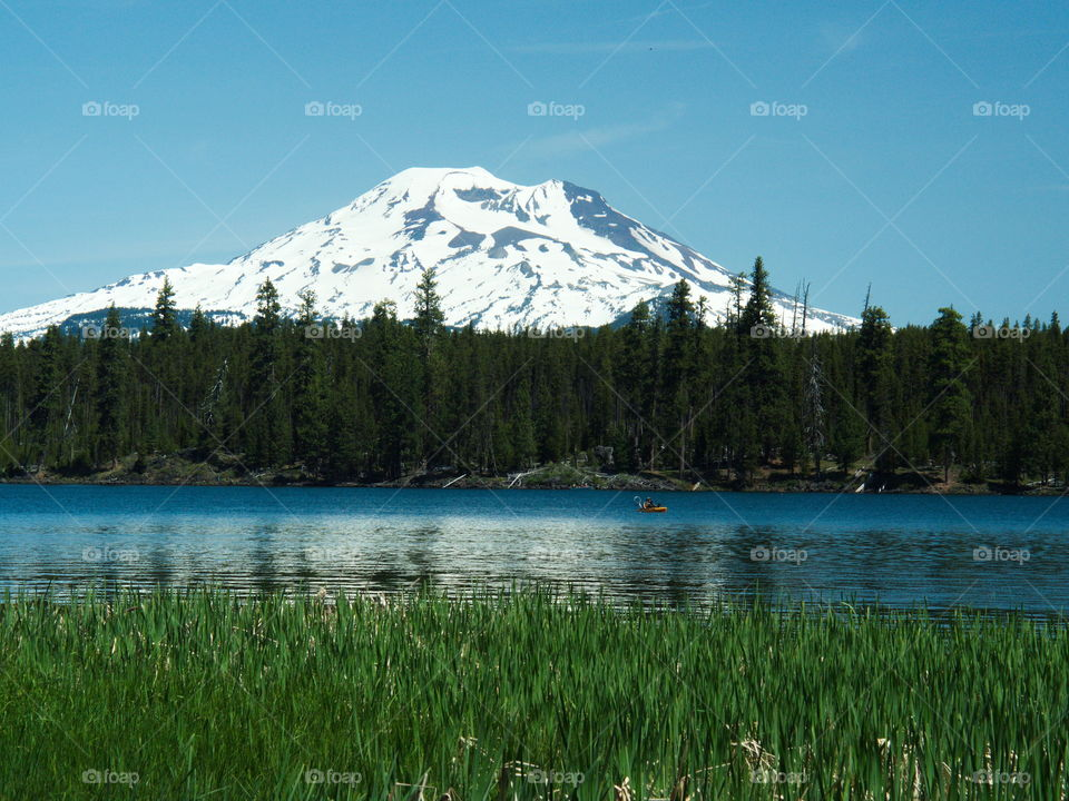The South Sister with snow behind lava lake on a sunny afternoon with a person kayaking
