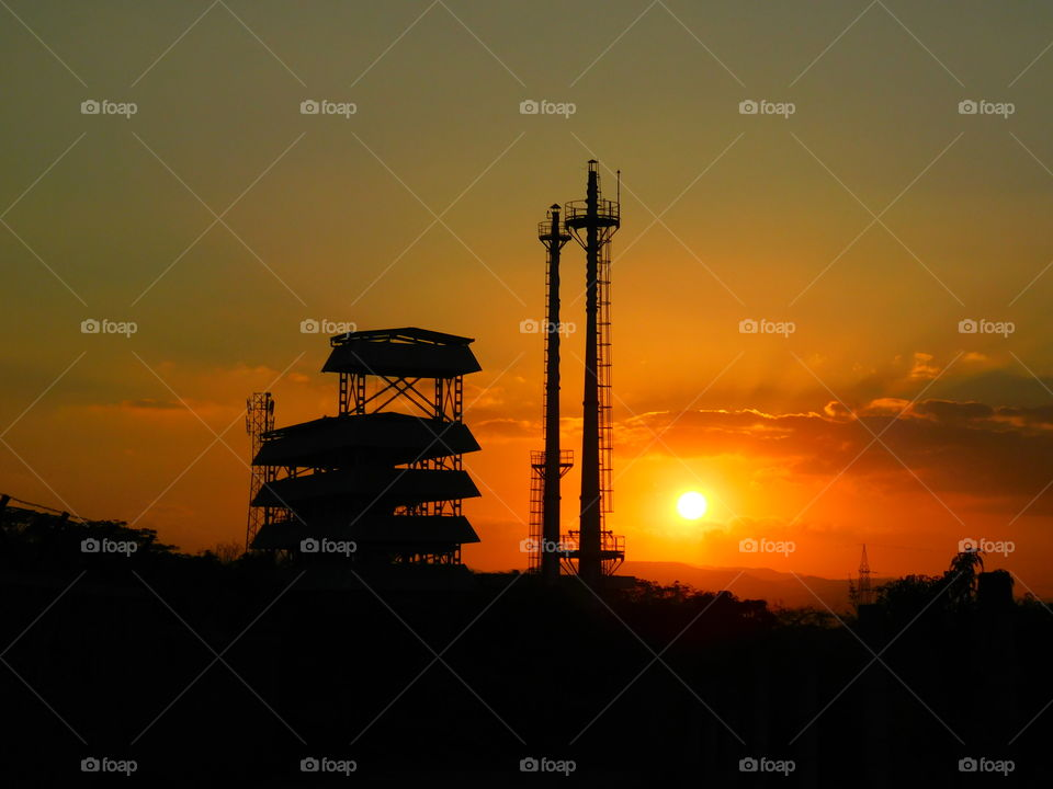 colourful sunset or dusk with golden light sky. It is a biggest source of energy. Industry or factory silhouette.