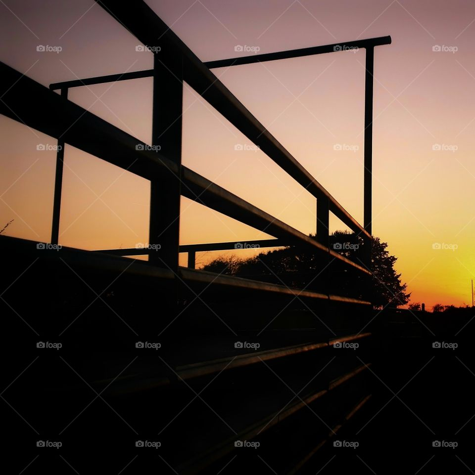 The rails and gate of a cattle pen at sunset form rectangles in the setting sun