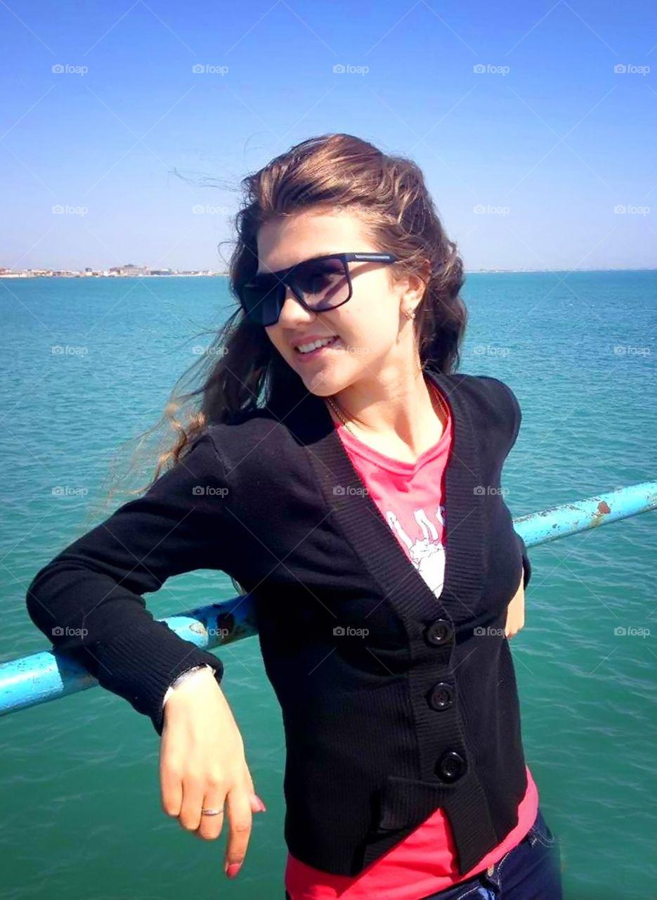 Beautiful girl is enjoying spring. Beautiful girl is smiling and is enjoying spring near the sea