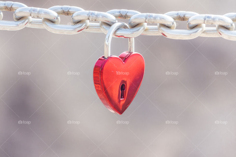 Red hart shaped padlock hanging from a steel chain