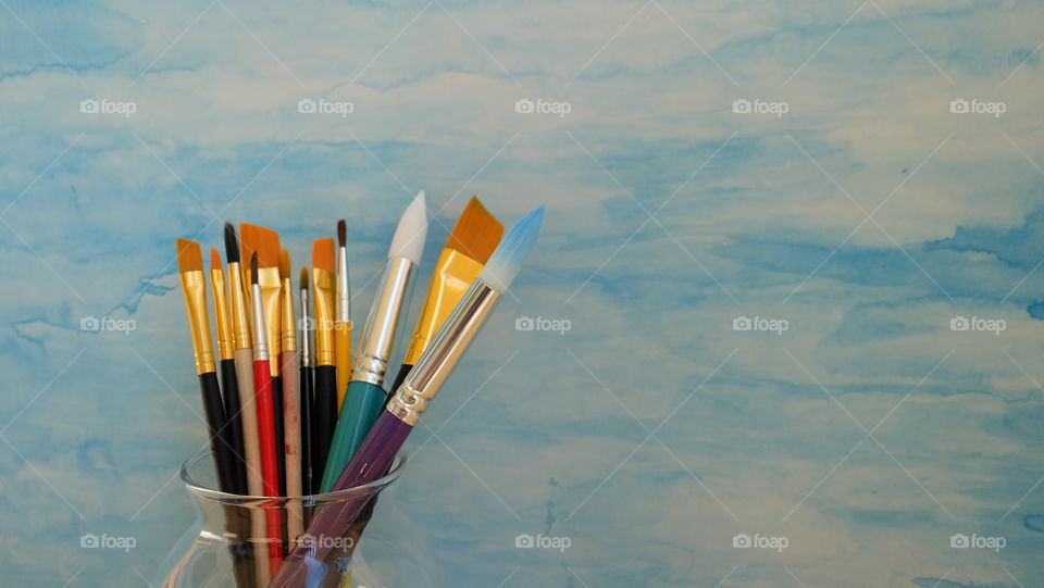Collection of paint brushes  against a blue background
