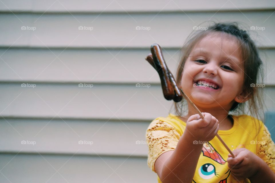 Small girl holding sausages in hand