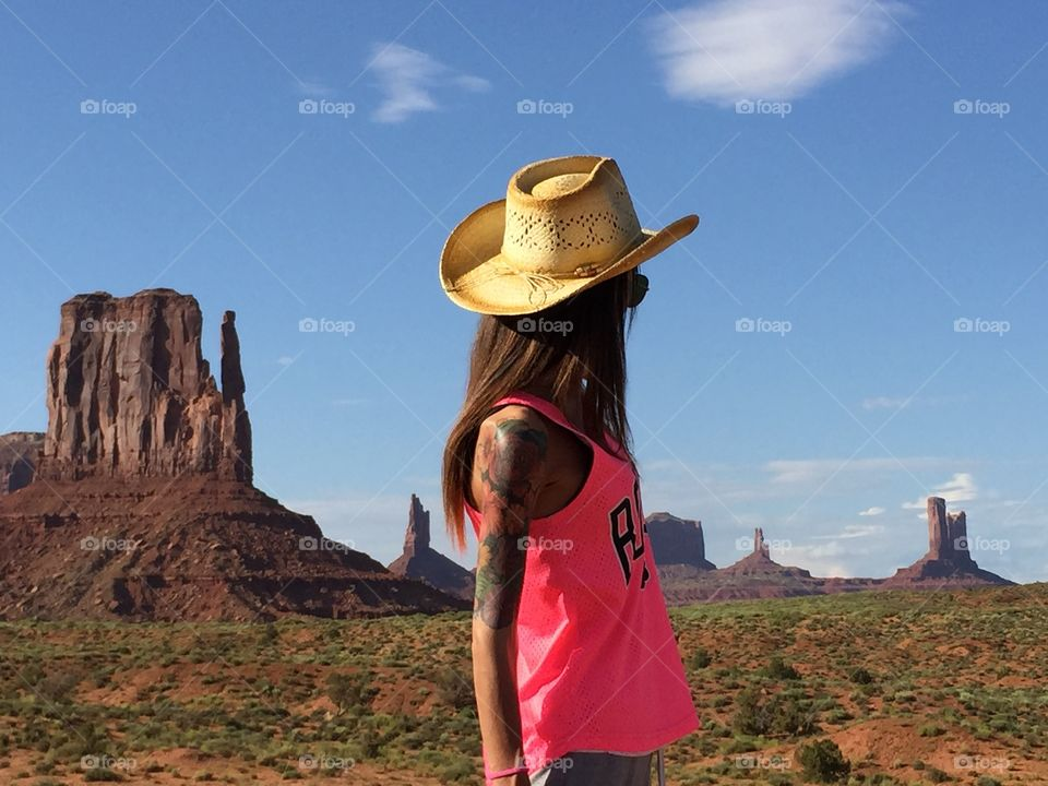 A young woman cowboy stand in the monument valley