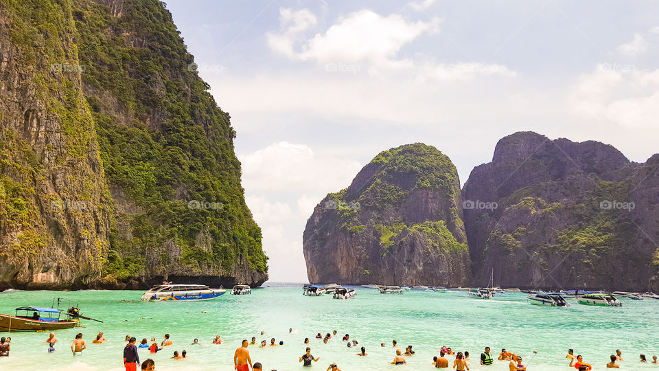 """Maya bay. Phi Phi (also known as Koh Phi Phi, Thai: หมู่ เกาะ พี พี) is a small archipelago located in the Andaman Sea, south of Thailand. It has become in recent years a very popular place for tourism, to the point that the expansion of hotel infrastructures are growing uncontrollably to accommodate so much tourism demand. The Phi Phi Islands (Thai: หมู่ เกาะ พี พี, rtgs: Mu Ko Phiphi, pronounced [mːː kɔʔ pʰīː.pʰīː]) are an island group in Thailand, between the large island of Phuket and the west Strait of Malacca coast of the mainland . The islands are administratively part of Krabi province. Ko Phi Phi Don (""""ko"""" (Thai: เกาะ) meaning """"island"""" in the Thai language) is the largest island of the group, and is the most populated island of the group, although the beaches of the second largest island, Ko Phi Phi Lee (or """"Ko Phi Phi Leh""""), are visited by many people as well. The rest of the islands in the group, including Bida Nok, Bida Noi, and Bamboo Island (Ko Mai Phai), are not much more than large limestone rocks jutting out of the sea. The Islands are reachable by speedboats or Long-tail boats most often from Krabi Town or from various piers in Phuket Province. The Phi Phi Islands (Thai: หมู่ เกาะ พี พี, rtgs: Mu Ko Phiphi, pronounced [mːː kɔʔ pʰīː.pʰīː]) are an island group in Thailand, between the large island of Phuket and the west Strait of Malacca coast of the mainland . The islands are administratively part of Krabi province. Ko Phi Phi Don (""""ko"""" (Thai: เกาะ) meaning """"island"""" in the Thai language) is the largest island of the group, and is the most populated island of the group, although the beaches of the second largest island, Ko Phi Phi Lee (or """"Ko Phi Phi Leh""""), are visited by many people as well. The rest of the islands in the group, including Bida Nok, Bida Noi, and Bamboo Island (Ko Mai Phai), are not much more than large limestone rocks jutting out of the sea. The Islands are reachable by speedboats or Long-tail boats most often from Krabi Town."""