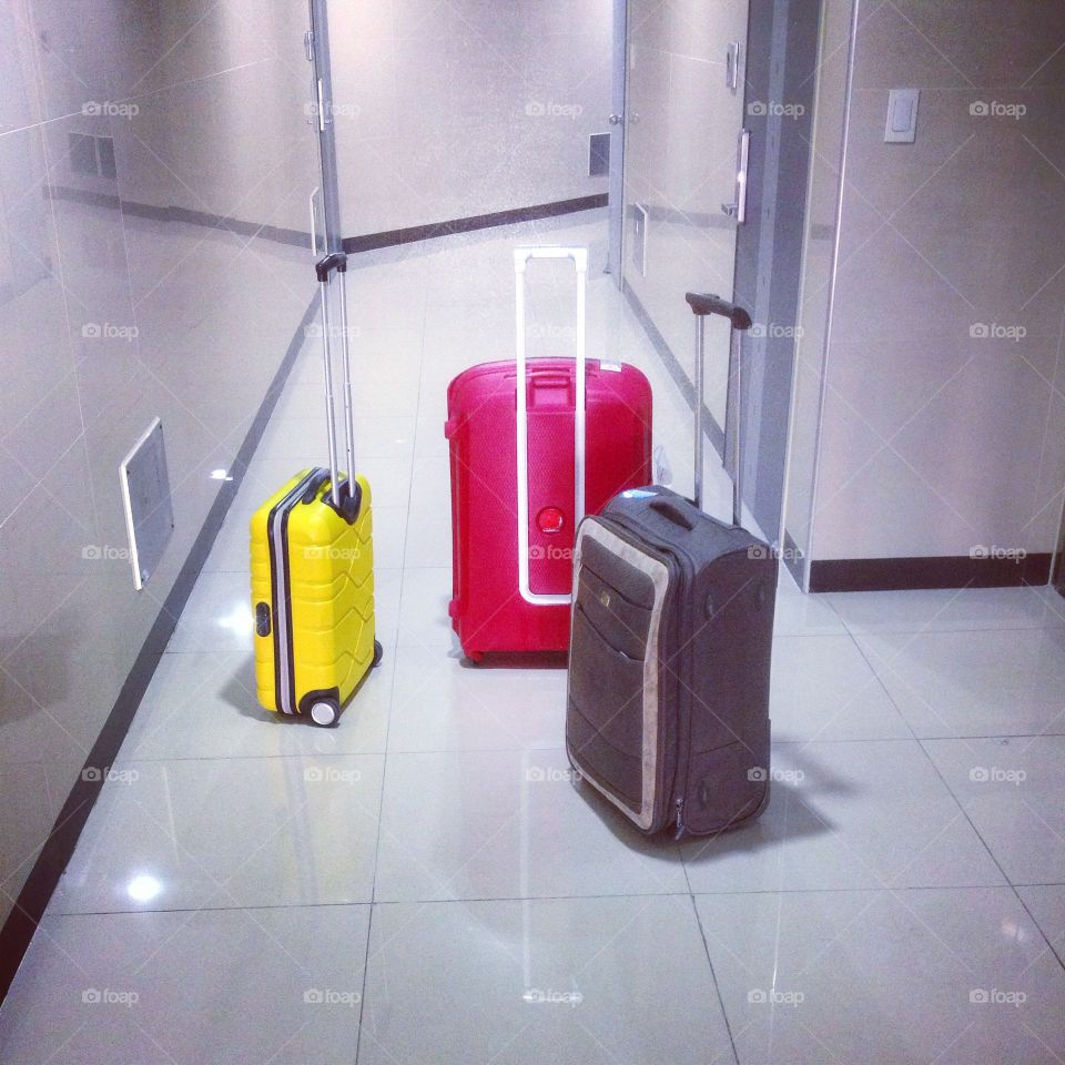 luggage waiting for travel. three suitcases in different colors and sizes standing in a corridor