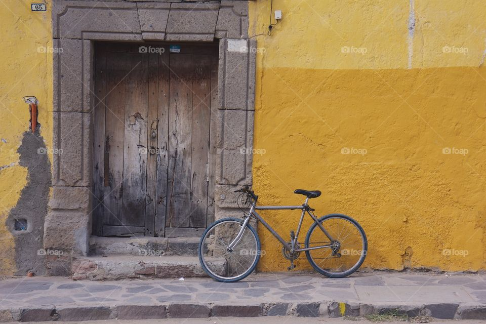A bicycle is parked outside a  colorful yellow concrete wall surrounding a worn wooden doorway.