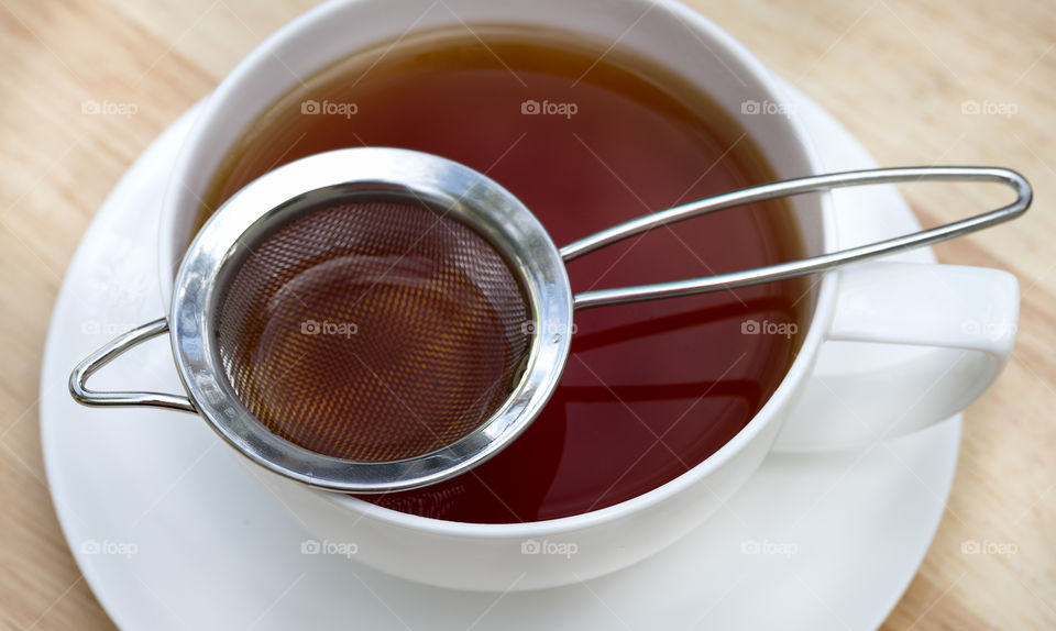 Overhead view of a strainer on teacup and saucer filled with black tea