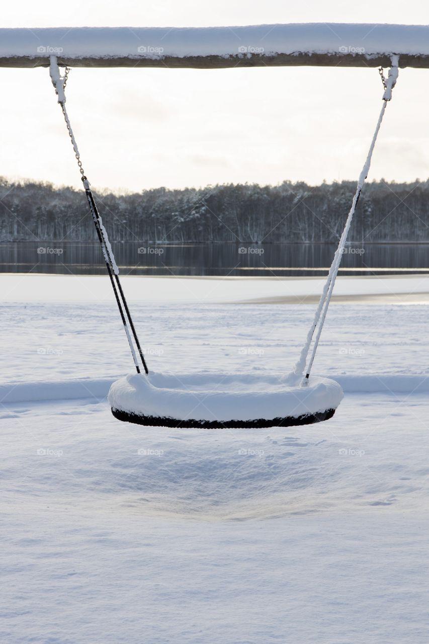 Snowy swing by the lake in winter wonderland at sunset - Vinter, gunga vid sjö täckt med snö vid solnedgång