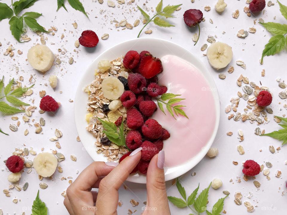 Female hand taking a red ripe raspberry from her healthy breakfast of yogurt, muesli and berries