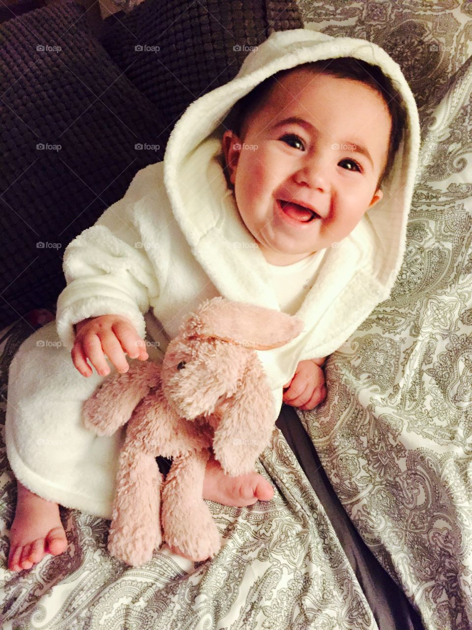 Smiling baby girl in a white fluffy robe