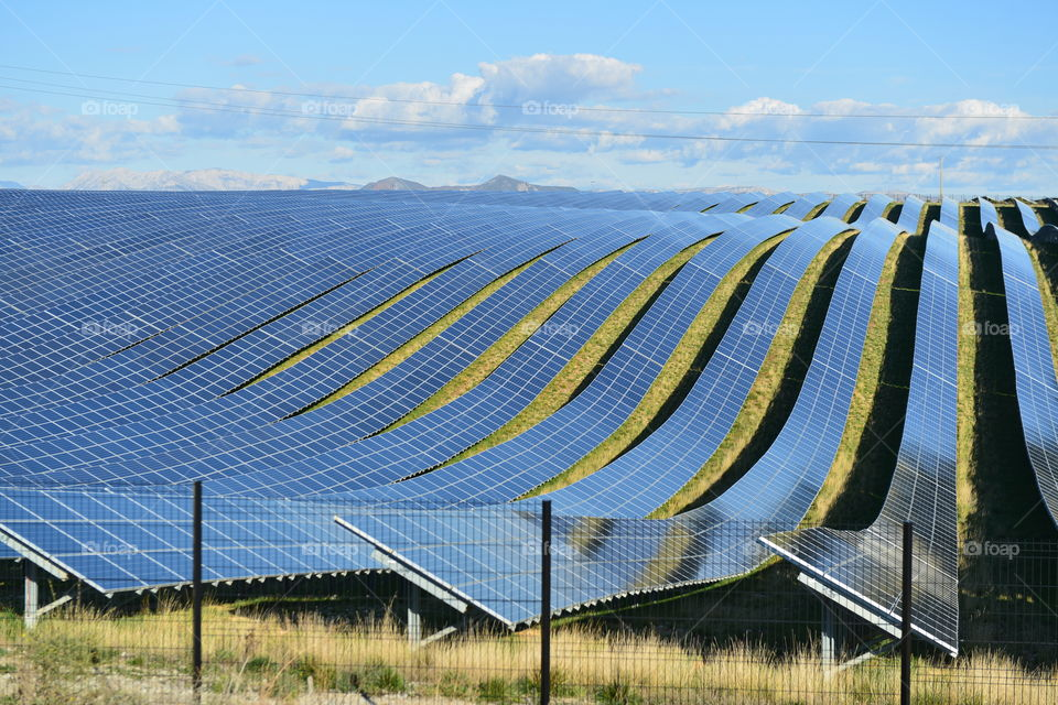 Green Energy Solar Farm with many Photovoltaic Panels across Acres of land