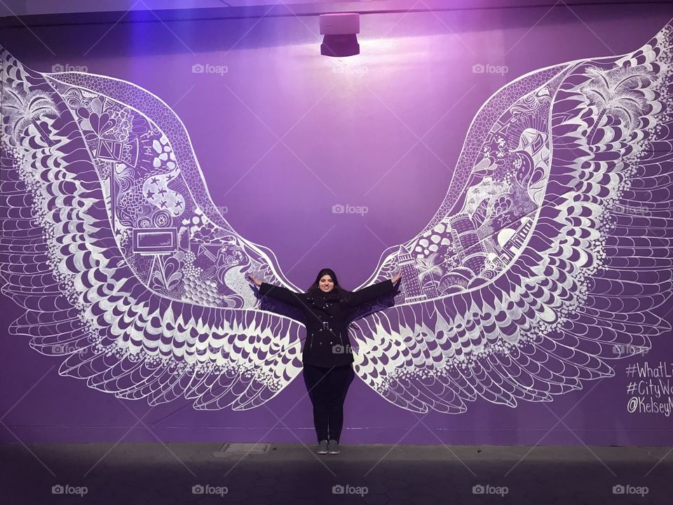 Girl with wings ready to fly. Arms wide open in front of a purple background.
