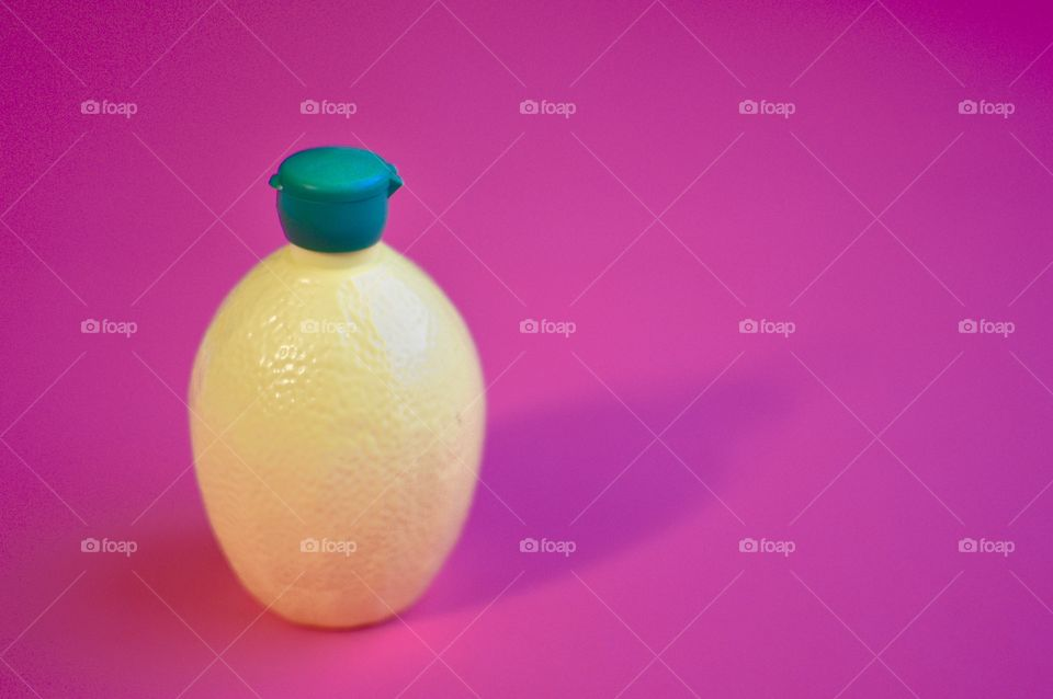 Contrasting flatlay with a bright pink background and a yellow and green plastic lemon juice bottle