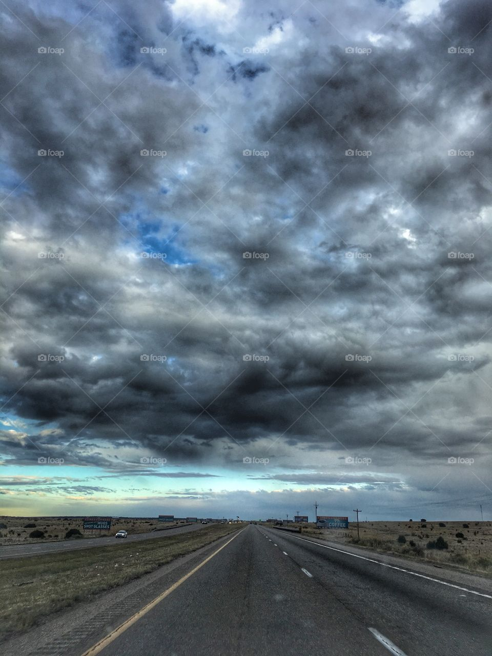 The grey road goes on underneath a grey sky. Traveling is a happy story