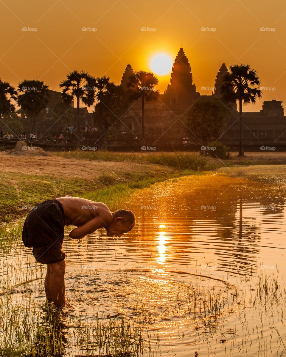 I was shooting sunrise at Angkor Wat when instantly an old man arrive and start shower himself in the pound. Unique moment