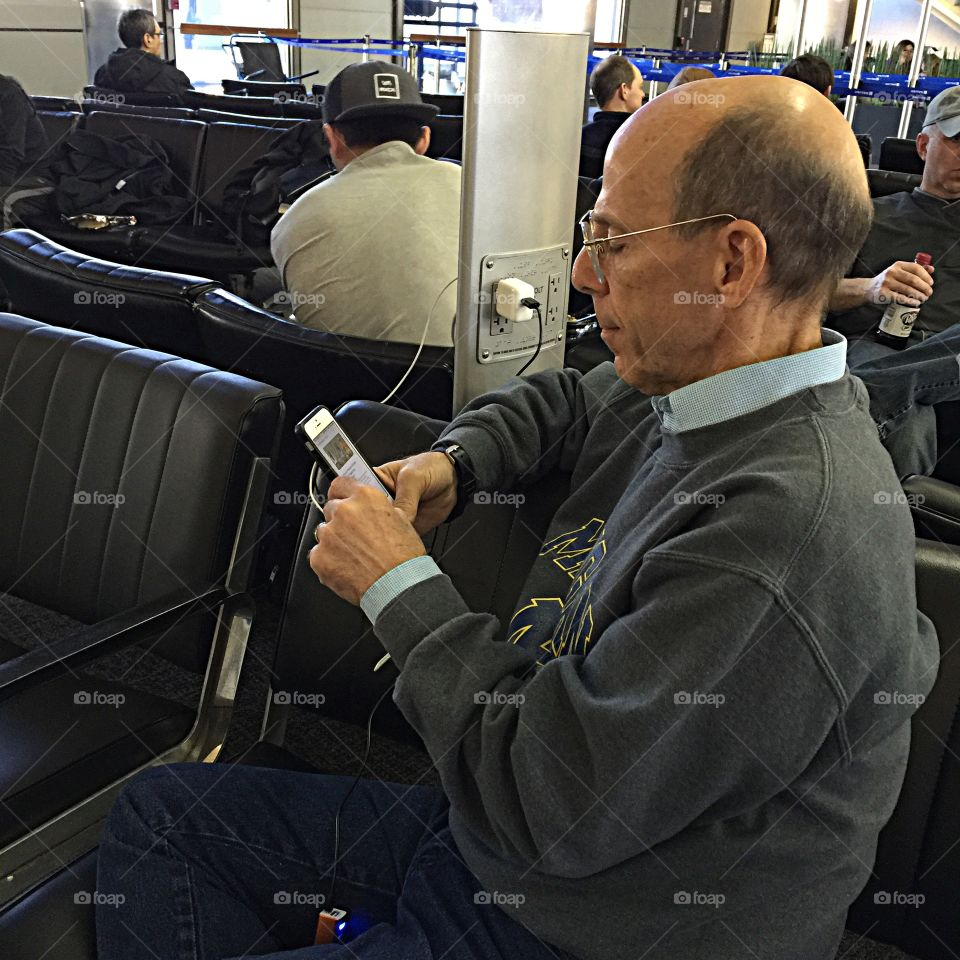 A man using technology at the airport