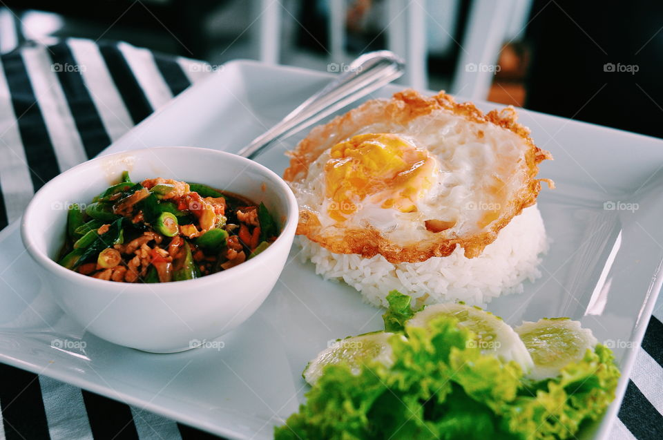 Thai Culture Dish. Sunny side up thai style, rice and stirred fried spicy vegatable with pork. This revolutionary dish is a signature dish throughout the world.