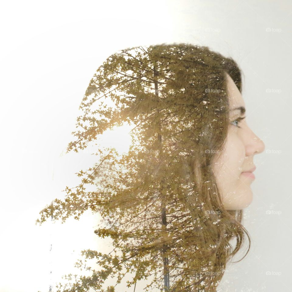 Double exposure of beautiful young woman and tree