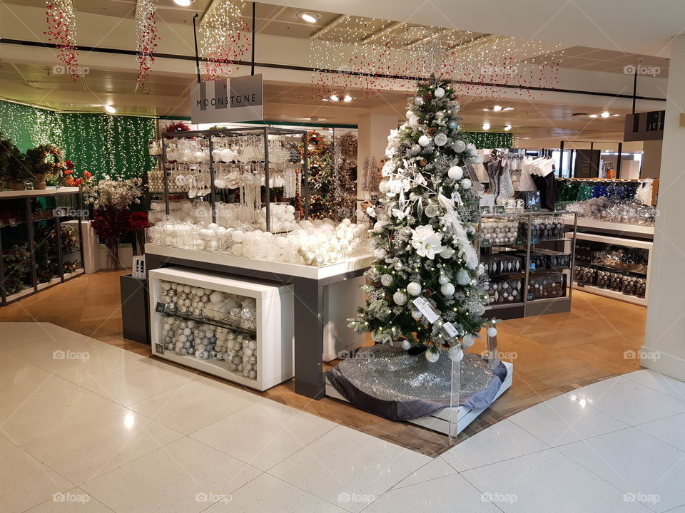 Christmas shop festive scene with decorated tree and white baubles at Peter Jones Sloane square Chelsea King's road London