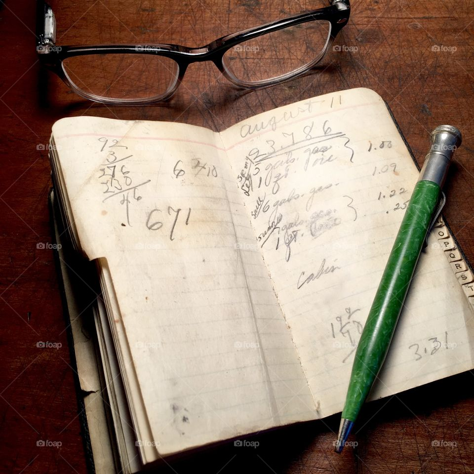 Vintage notebook and mechanical pencil with spectacles on wood desk.