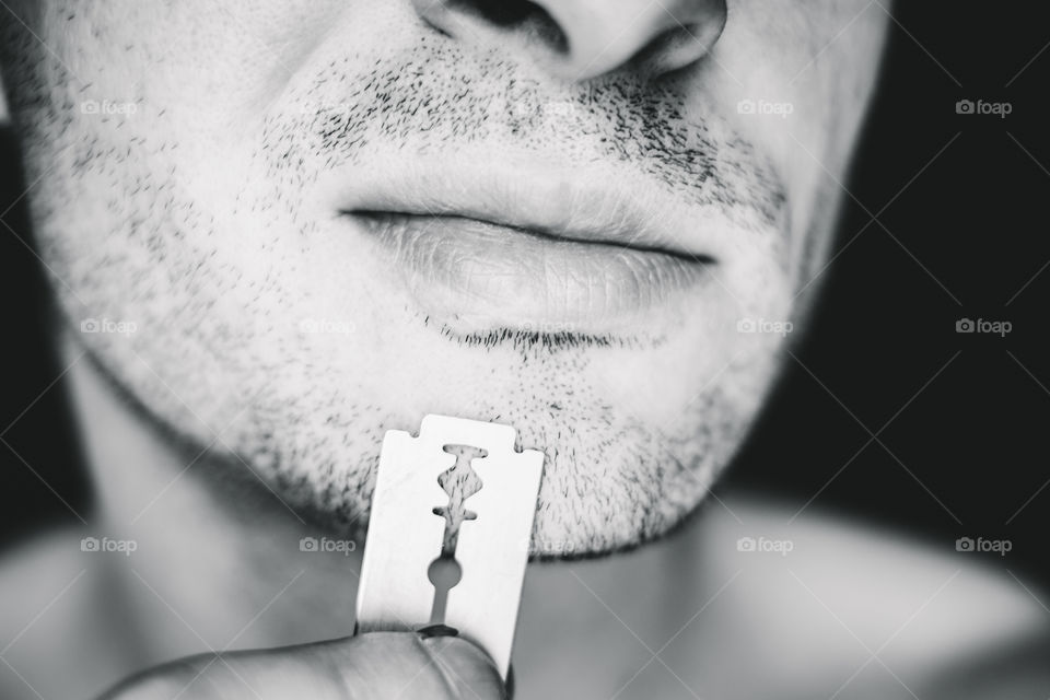 Close-up of beard man' face with stainless razor blade