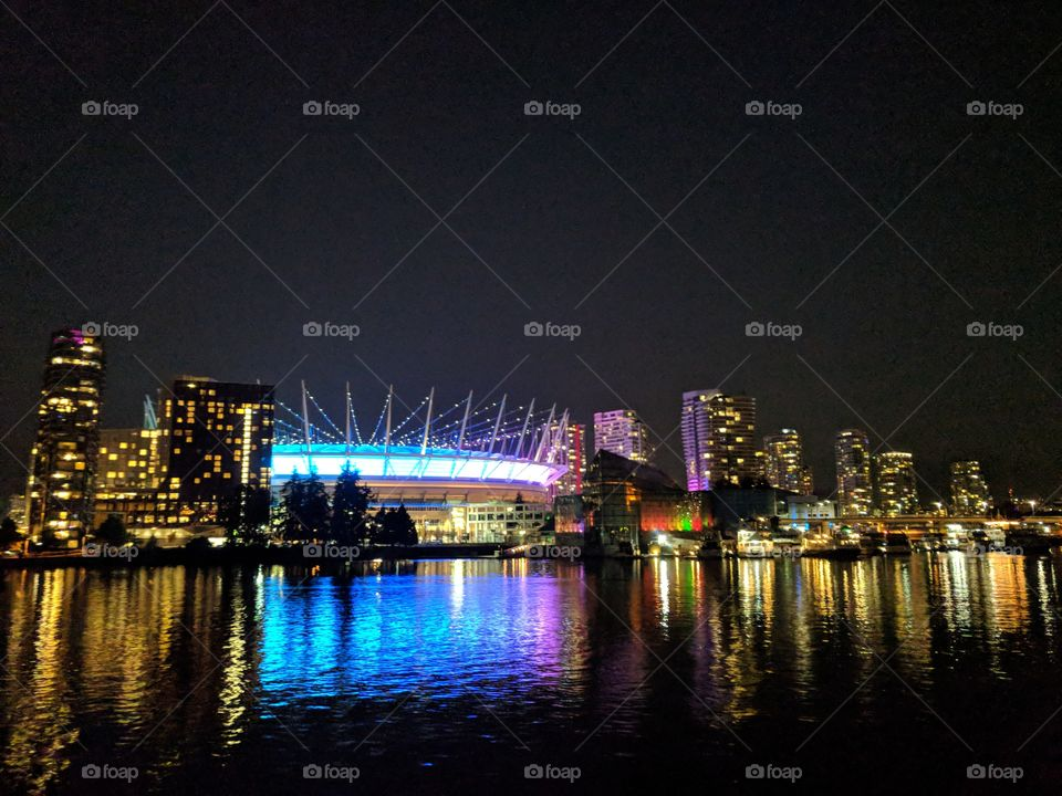 Stunning lit up stadium downtown with reflection in the water