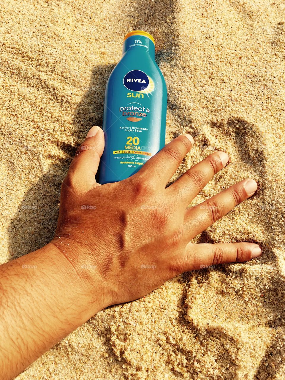Hand holding bottle of Nivea Sunscreen Protector in the beach's sand