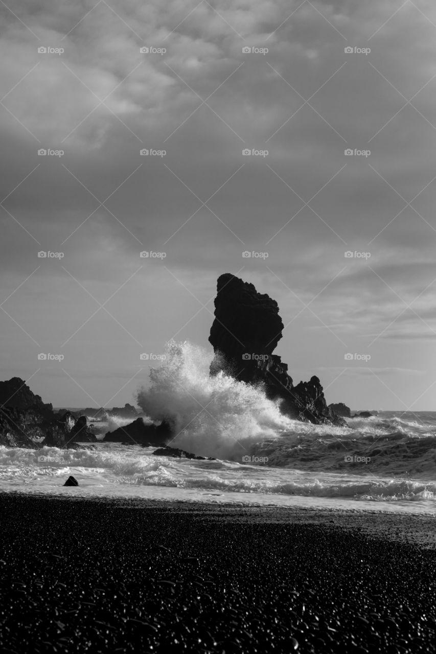 White on black. White waves break on black rocks in Snæfellsnes in Western Iceland.