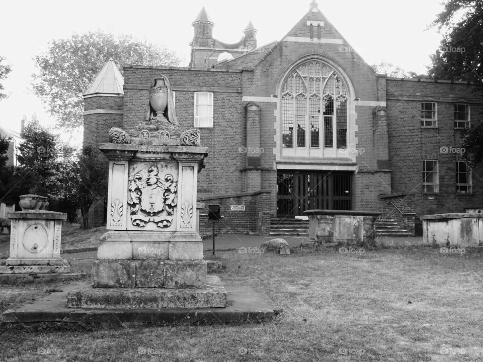 An old church with headstones in the yard in England.