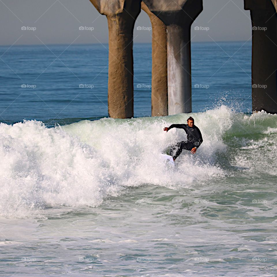 Surfer on a wave in Manhattan Beach, CA