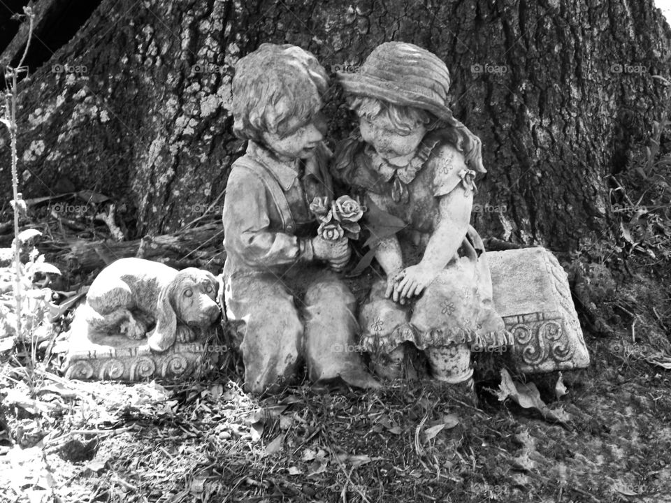 Black and white boy and girl garden statue with a puppy