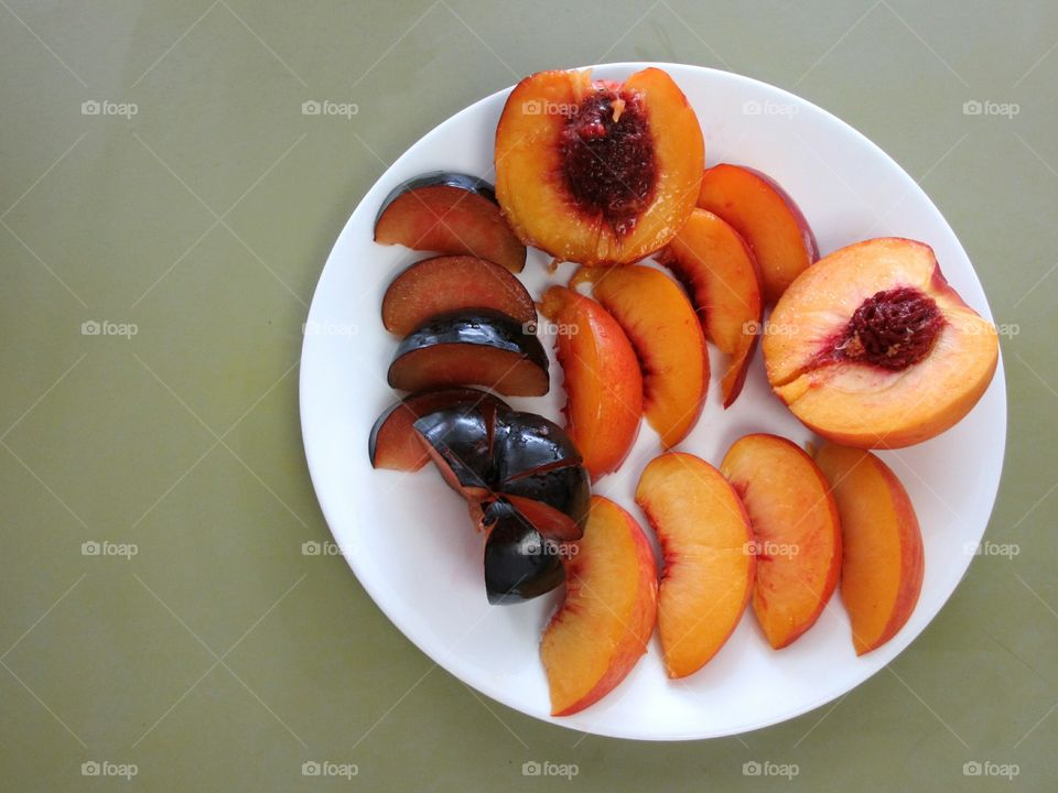 White plate with sliced peach, nectarine and plum