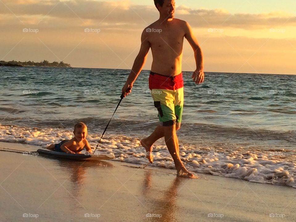 Boogie board training . Dad pulling his son on a boogie board in Hawaii