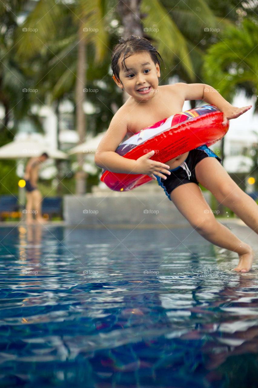 Happy kid falling into the pool. Thithi having fun