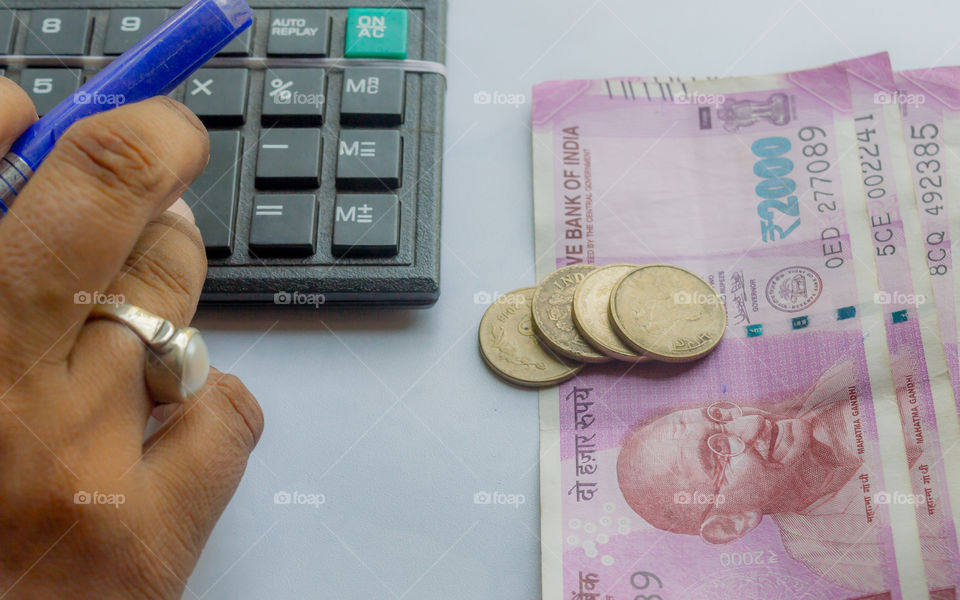Cropped hand of a woman checking account with calculator and holding a pen. Indian currency notes and coins are on the side of table. Corporate business concept.