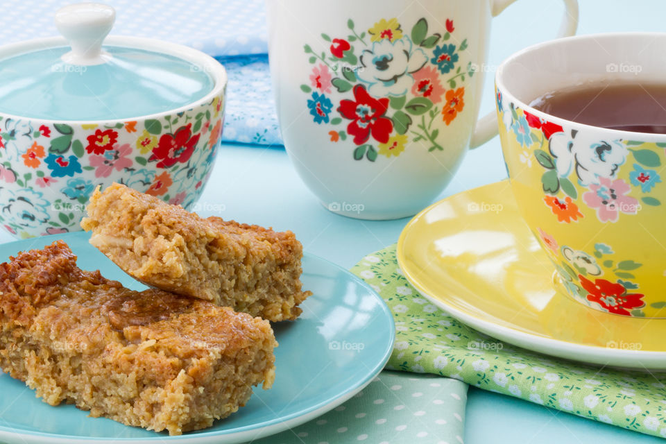 Afternoon tea with cake and flapjack in floral crockery.