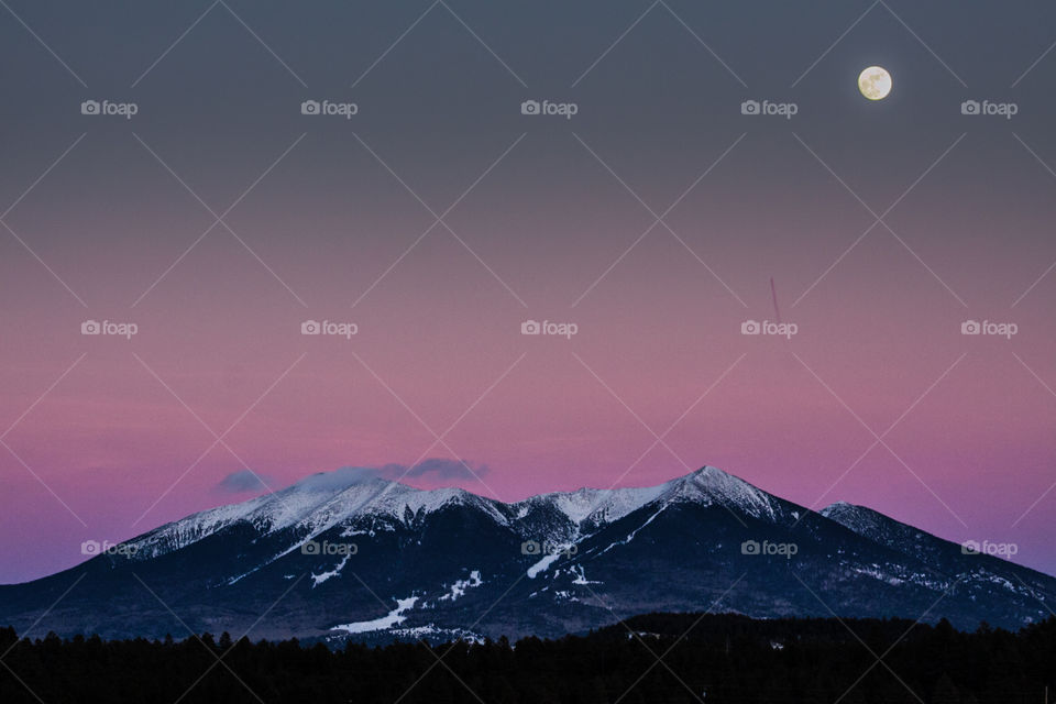 Snow covered mountain range and moon