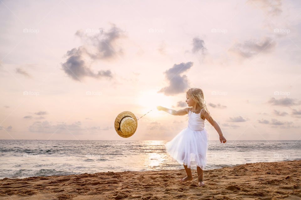 Beautiful little girl playing on the sandy beach on sunset