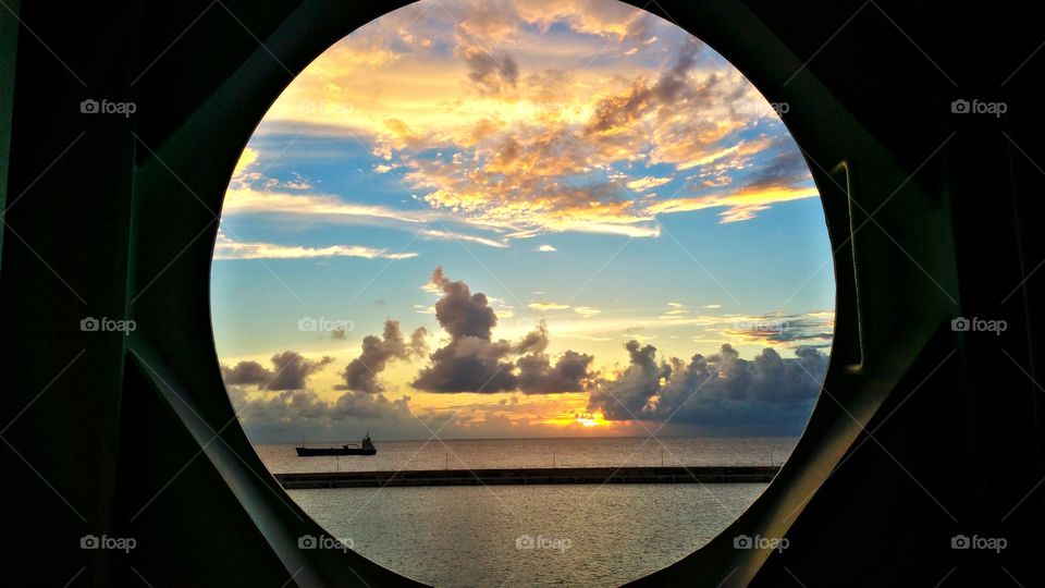 view of sunset through port hole of ship.. Barbados