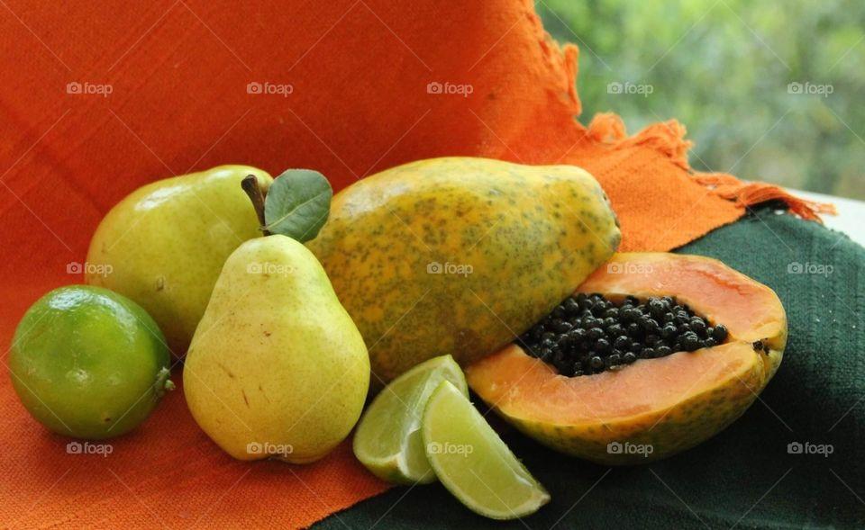 Papaya, pear and lemon on an orange and green background