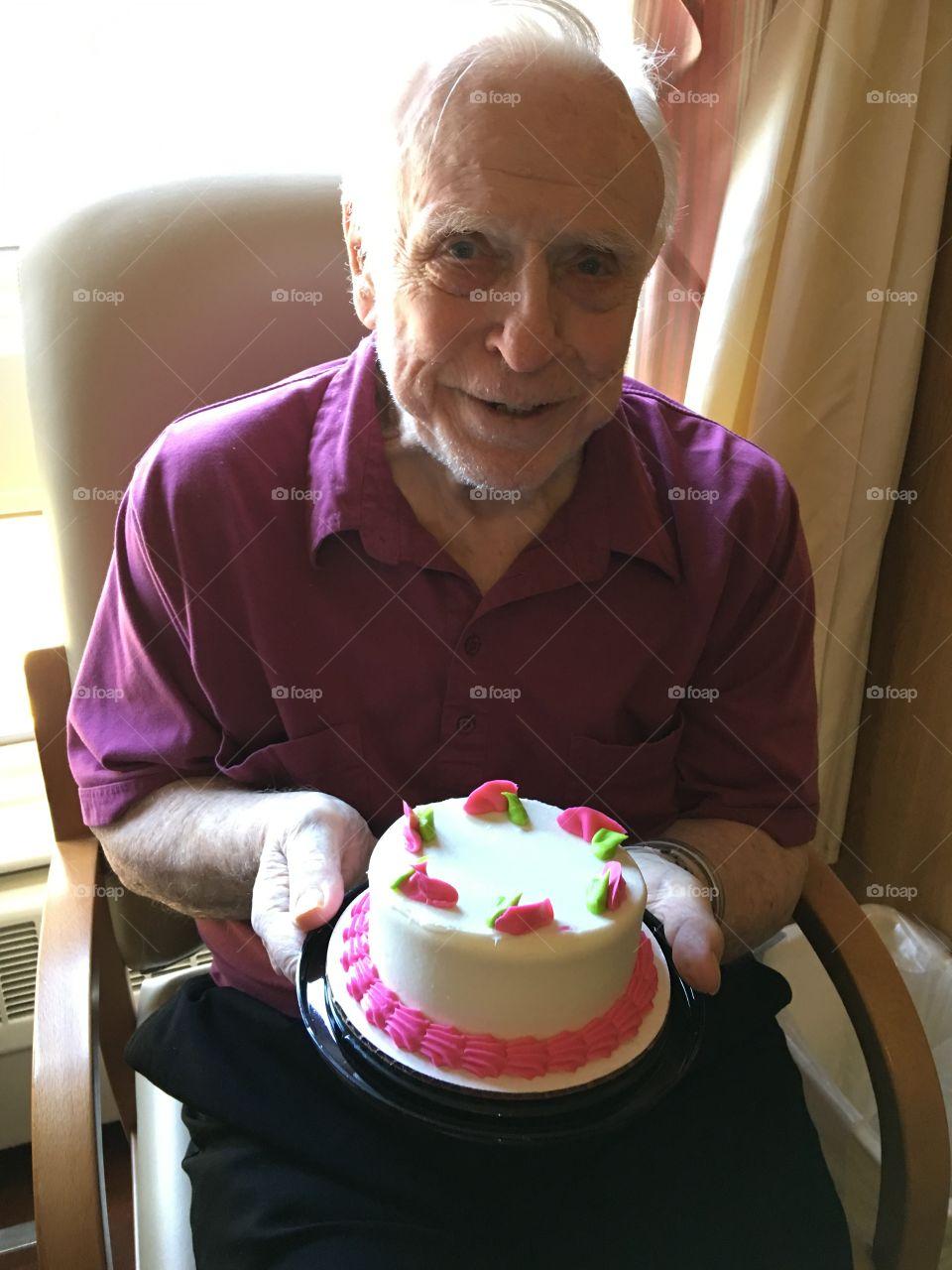 Senior man holding cake in hand