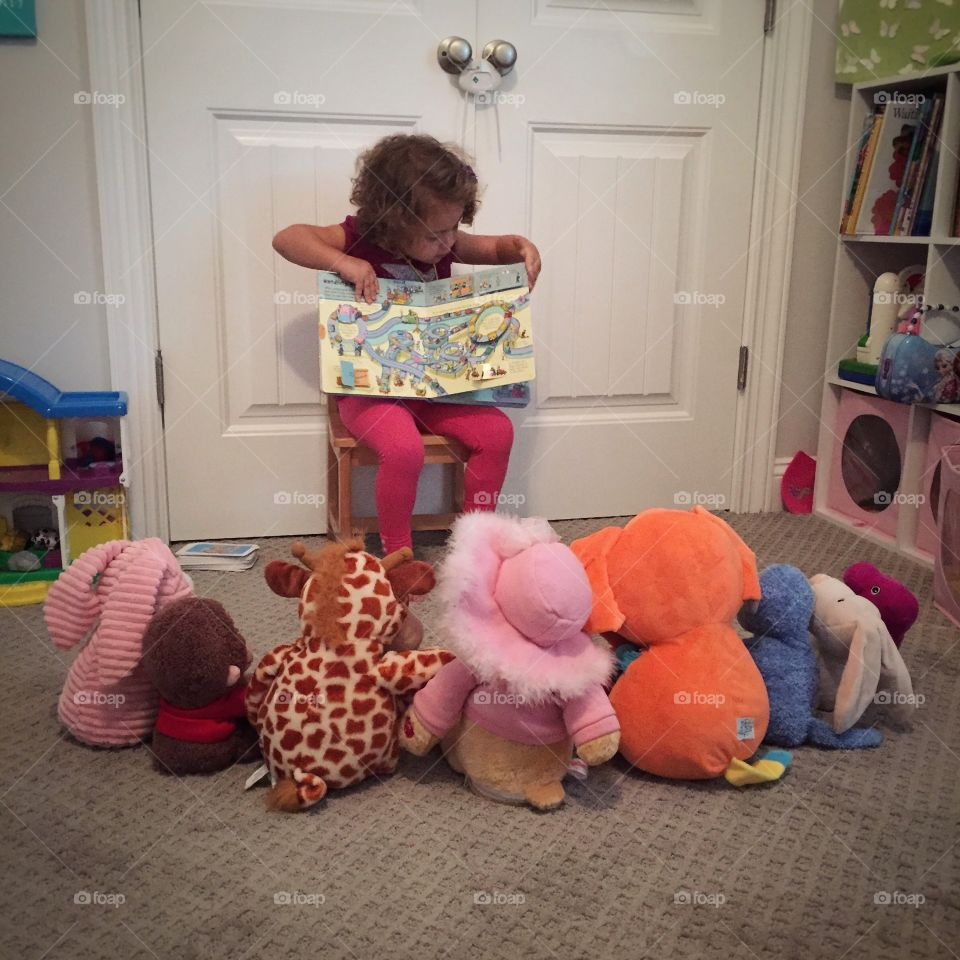 Playing School. A toddler girl playing school with her stuffed animals.