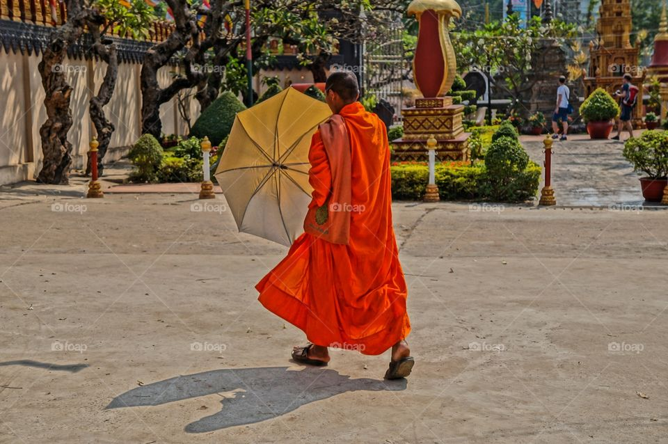 Escaping the heat. Monk in Cambodia unfold his umbrella to cover from heat