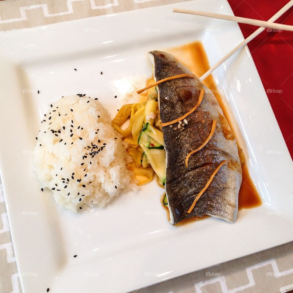 Fish dinner. Red snapper over a bed of ginger and zucchini with sticky rice.
