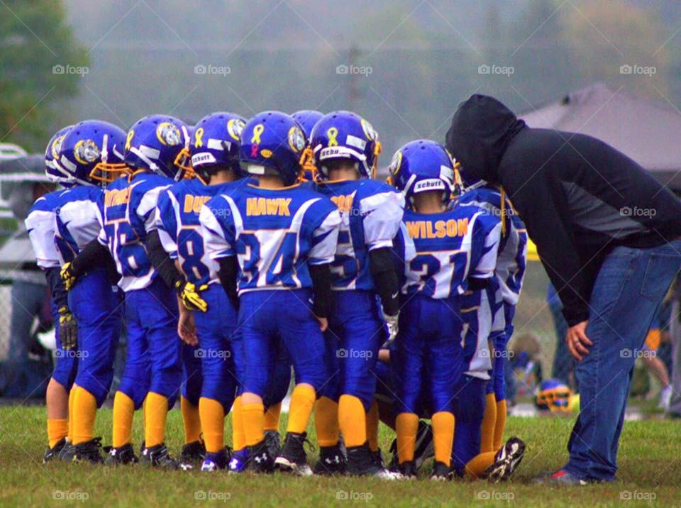 Huddled Up. Pee-wee football team in a huddle.