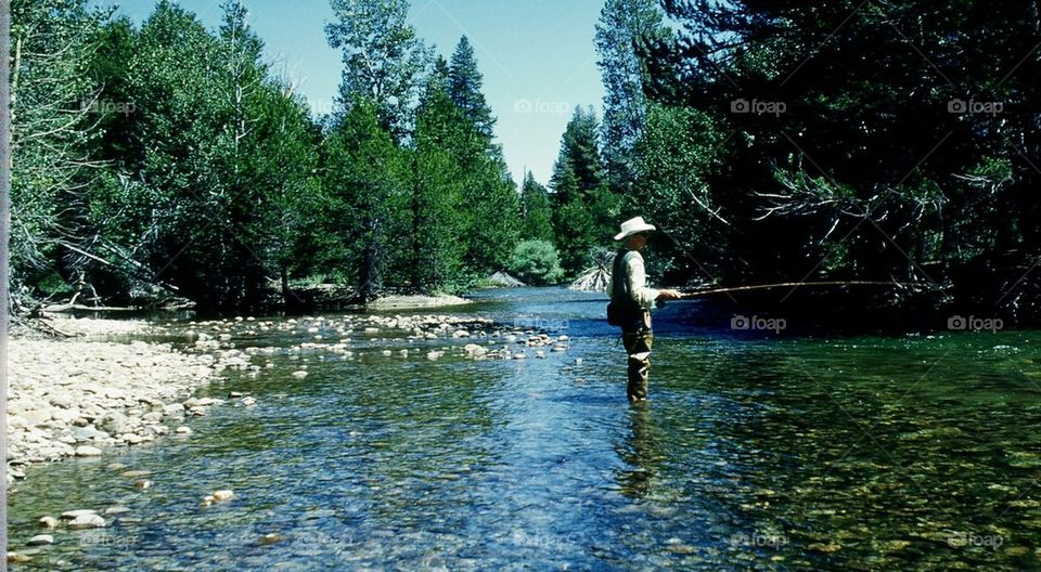 Uncle fishing in river. Beautiful clear water peace of mind