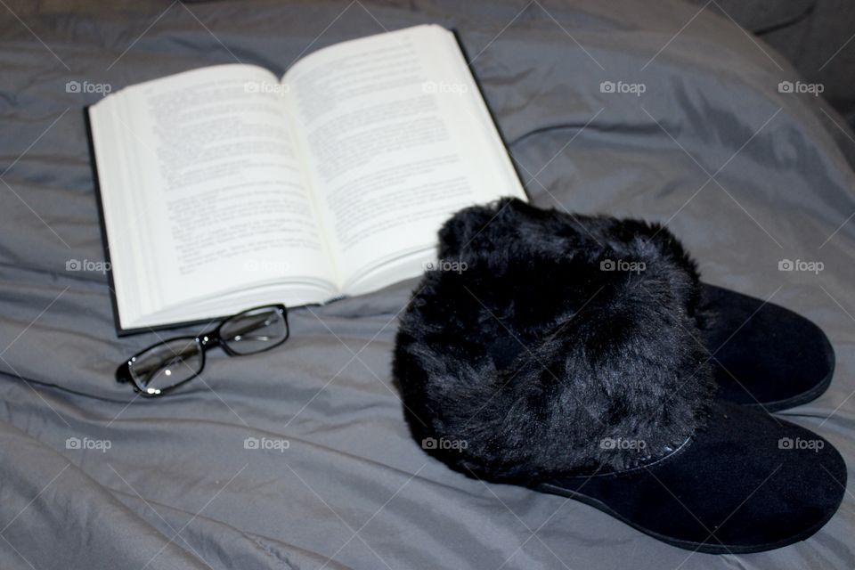 Book, glasses, and black slippers