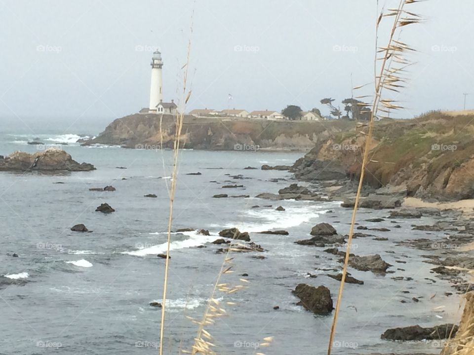Foggy view of a distant lighthouse. Pigeon Point lighthouse.